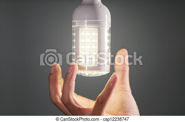 hand replacing led light bulb - csp12238747