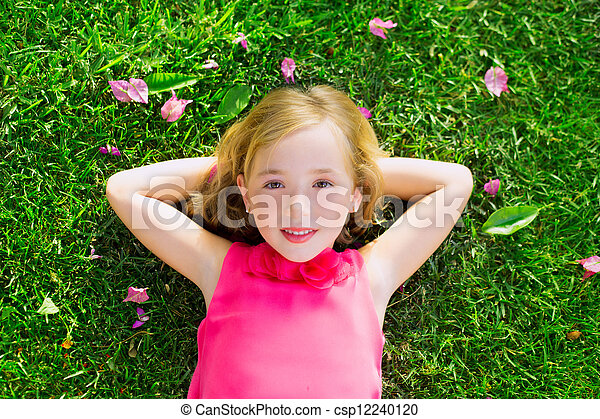 Blond kid girl lying on garden grass smiling aerial view - csp12240120