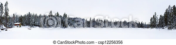 Panorama of frozen lake with log cabin - csp12256356