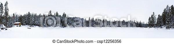 Panorama of frozen lake with log cabin - csp12256356
