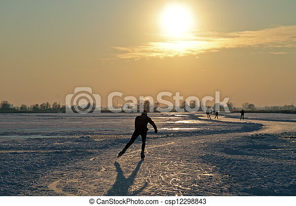 Ice skating in the countryside from the Netherlands at sunset - csp12298843