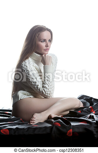 Young woman in sweater sitting on bed - csp12308351