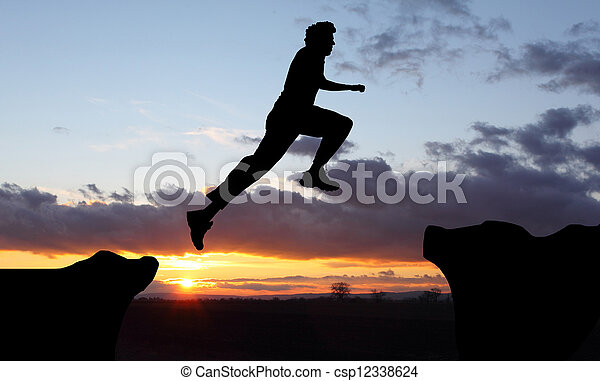 Silhouette of hiking man  jumping over the mountains at sunset - csp12338624