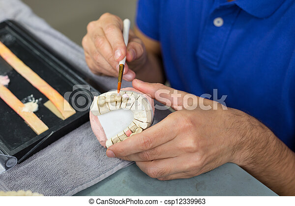 Closeup of dental technician applying porcelain - csp12339963