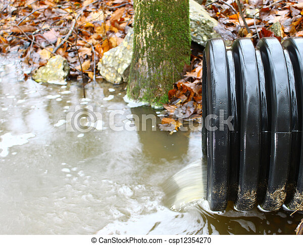 A waste water drainage pipe re-routing the water flow and polluting the environment at the same time  - csp12354270