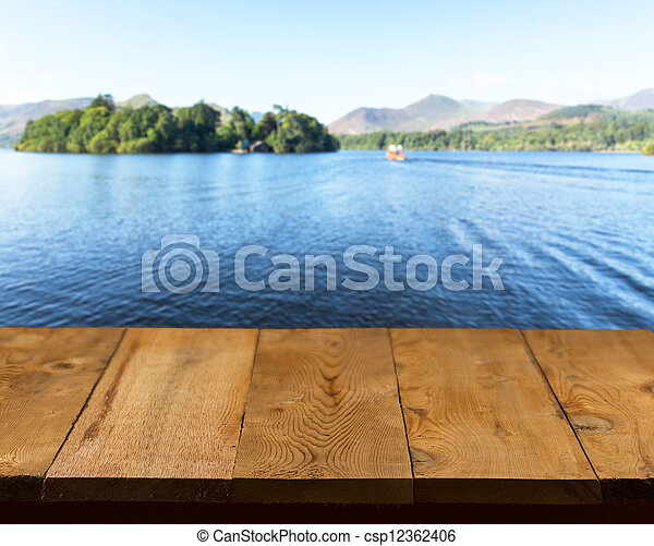 Old wooden table or walkway by lake - csp12362406