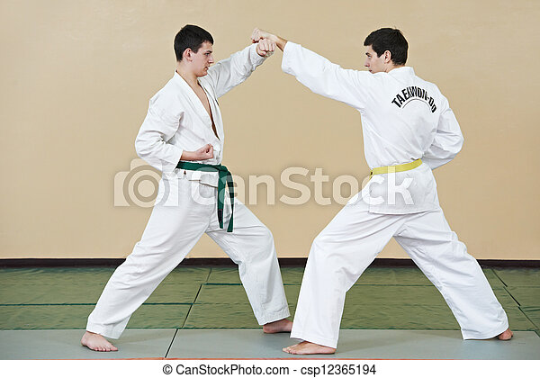 Two young adult people in kimono training taekwondo martial art at gym