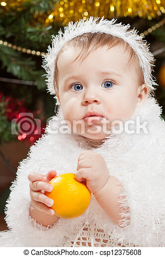 Happy little baby girl playing with fruits