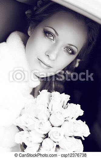 Beautiful bride woman portrait with bridal bouquet posing in her wedding day - csp12376738