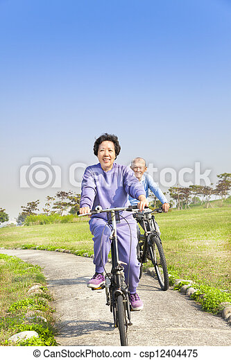 asian seniors couple biking in the park - csp12404475