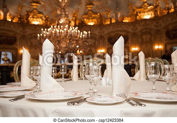 restaurant dinner table place setting: napkin, wineglass, plate - csp12423384
