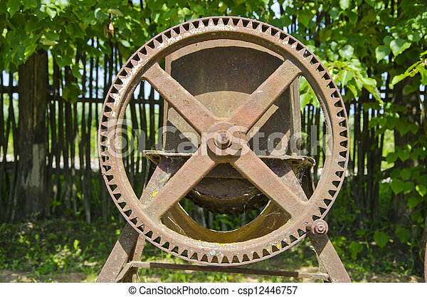 old agriculture metal wheel in garden - csp12446757