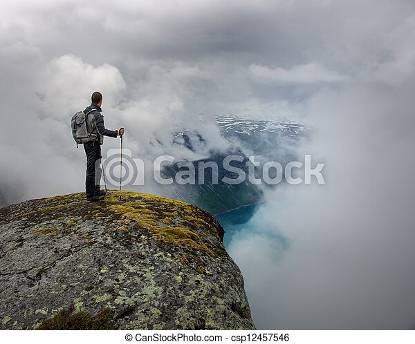 Man with hiking equipment standing on rock's edge - csp12457546