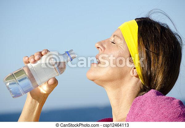 Exercising mature woman drinking water ocean
