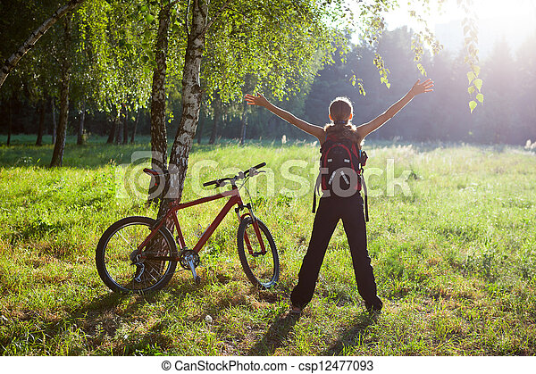 Excited girl cyclist standing in a spring park with hands outstretched. Sunny outdoor - csp12477093