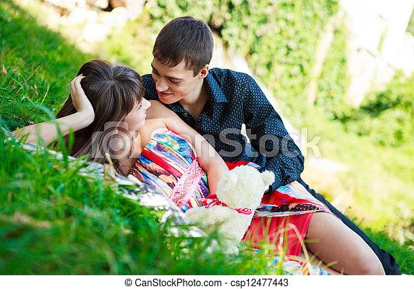 Happy couple flirting in a sunny summer park - csp12477443