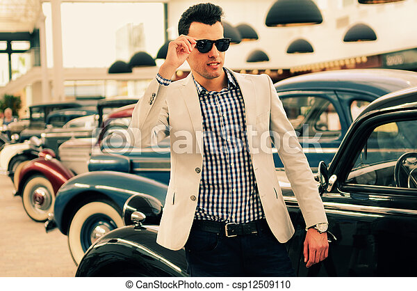 Attractive man wearing jacket and shirt with old cars