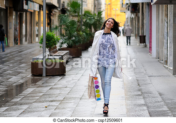 Portrait of a beautiful woman with shopping bags walking along a commercial street