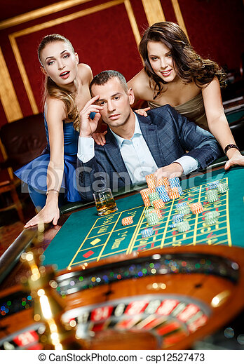 Man with two girls playing roulette at the gambling house - csp12527473