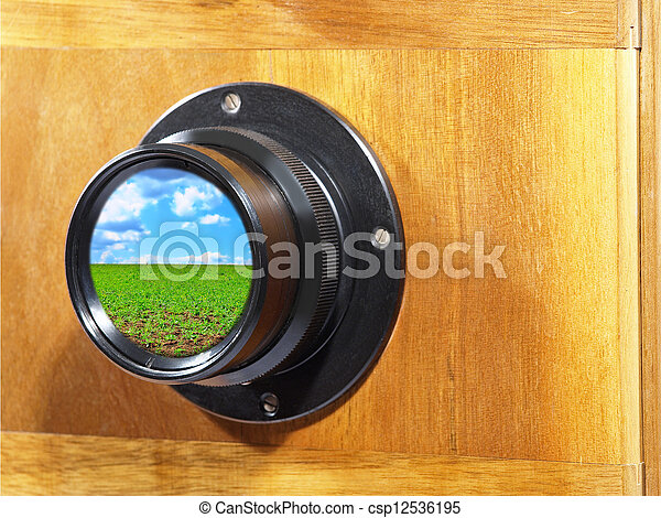 Camera lens with blue sky and green grass reflection.
