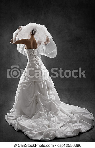 Bride in wedding luxury dress, back view, raised hands up. Black background - csp12550896