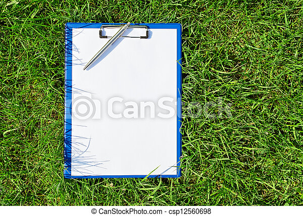 Blue medical clipboard with a pen over lush green grass