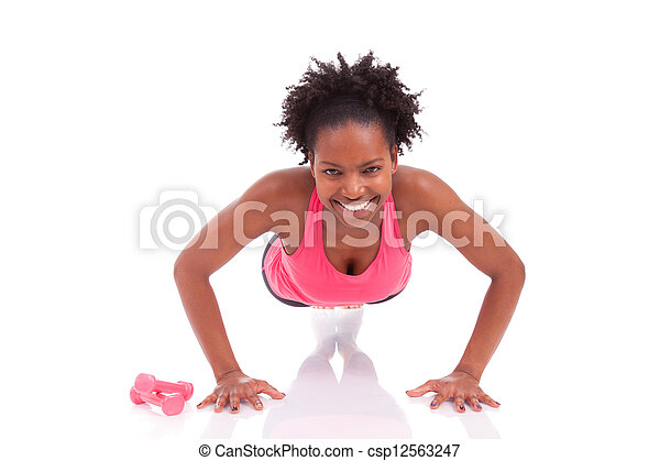Young beautiful african fitness woman doing push up exercises on floor, isolated on white background - csp12563247