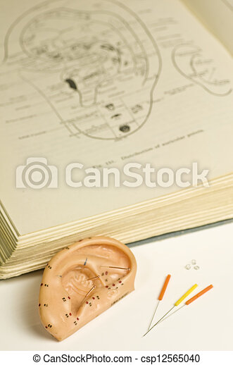 ear acupuncture model, textbook and acupuncture needles