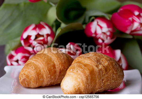 Two croissants next to a bouquet of tulips