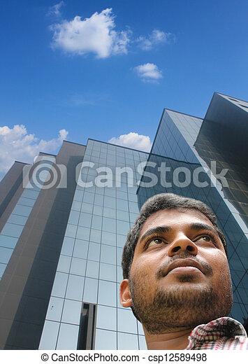 Handsome smart businessman/executive with modern building background looking forward confidently about future. The young adult is of Indian origin  - csp12589498
