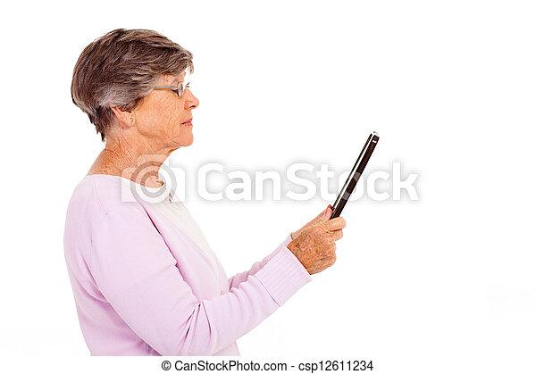 elderly woman reading book - csp12611234