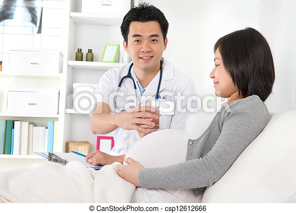 Mid adult female patient for medical check up at clinic with doctor on background - csp12612666