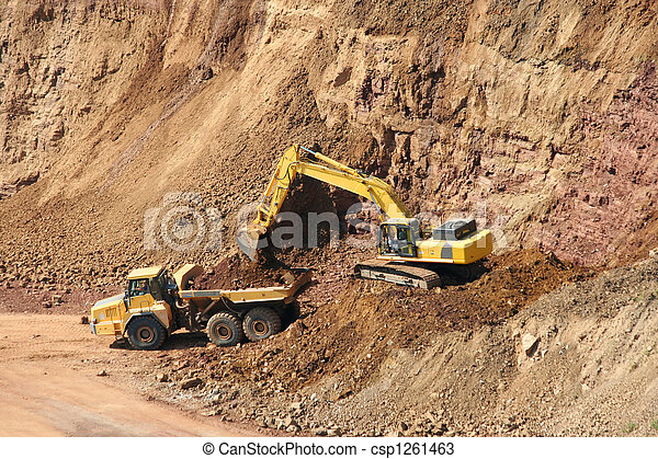 Backhoe and dumptruck at rock quarry - csp1261463