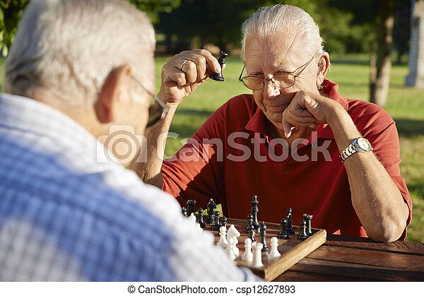 Active retired people, two senior men playing chess at park - csp12627893
