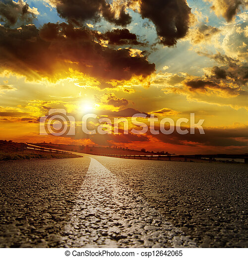 asphalt road and dramatic sunset over it - csp12642065