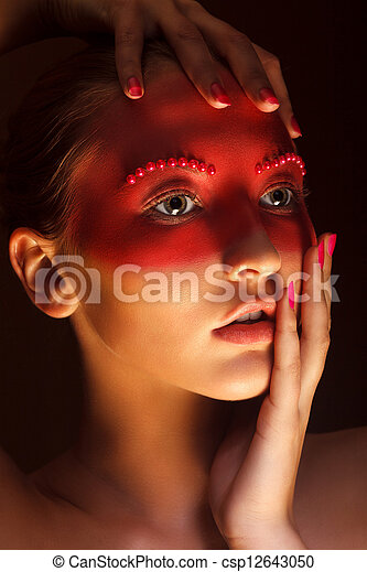 Fashion Art Concept. Beauty Woman Face with Red Painted Mask - csp12643050