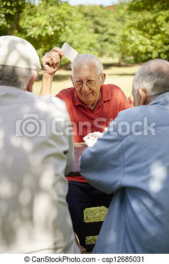 Active seniors, group of old friends playing cards at park - csp12685031