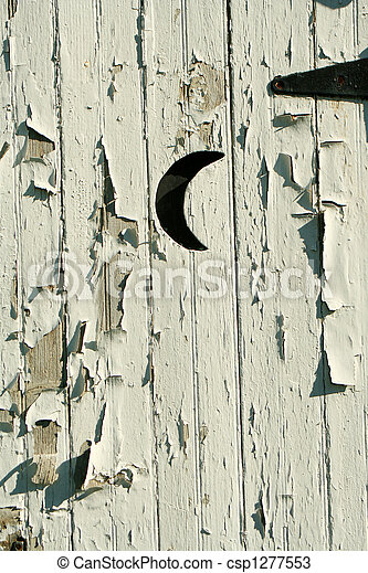 Old white outhouse moon door - csp1277553