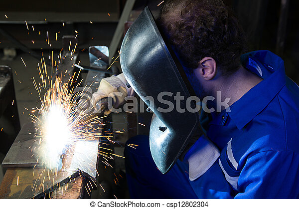 Man welding steel creating many sparks - csp12802304