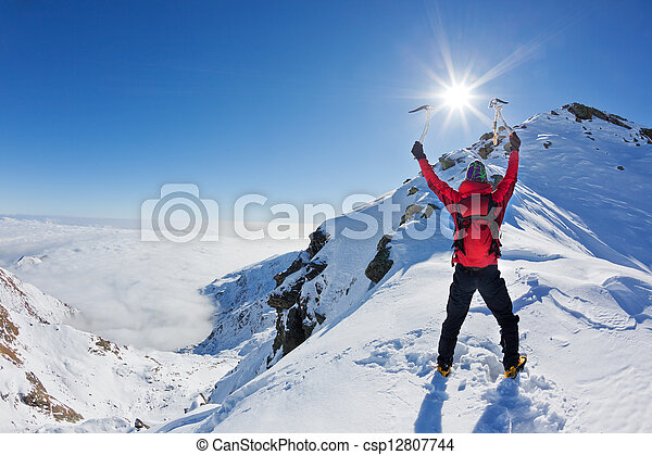 Mountaineer reaches the top of a snowy mountain in a sunny winter day. - csp12807744