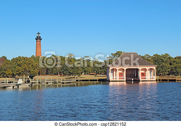 The red brick structure of the Currituck Beach Lighthouse and the pink boathouse at Currituck Heritage Park near Corolla, North Carolina - csp12821152