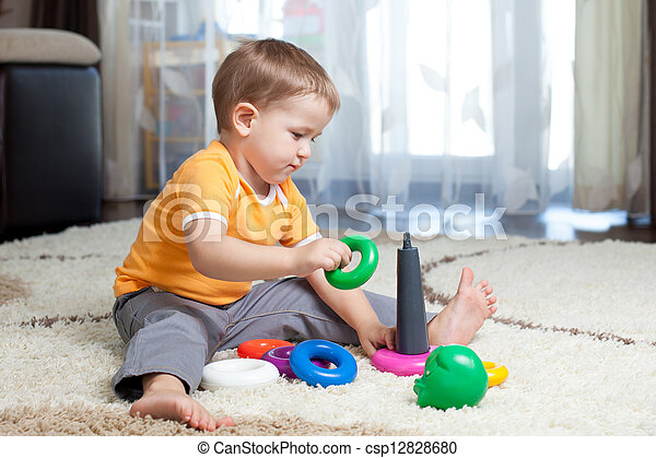 Child boy playing with toy at home. - csp12828680