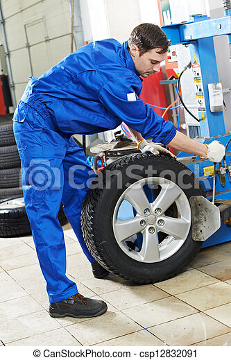 repairman mechanic at wheel replacement - csp12832091