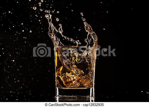 Glass of whiskey with splash, isolated on black background - csp12832935