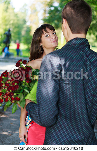 Young man gift a woman a bouquet of red roses in a summer park - csp12840218