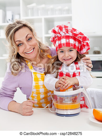Happy woman and child making fresh orange juice