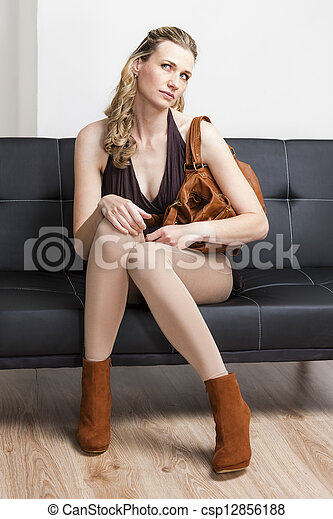 woman wearing fashionable brown shoes with a handbag sitting on sofa - csp12856188