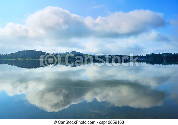 Lake banks and clouds reflection in calm water - csp12859163