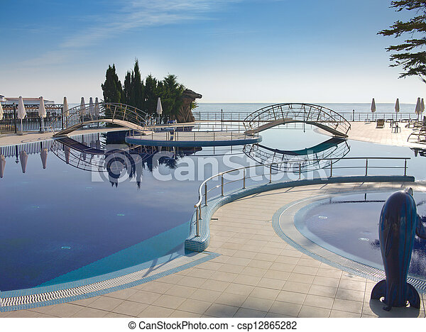 swimming pool with tree, bridges and white umbrella - csp12865282