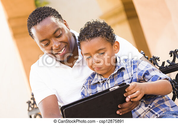 Mixed Race Father and Son Using Touch Pad Computer Tablet - csp12875891